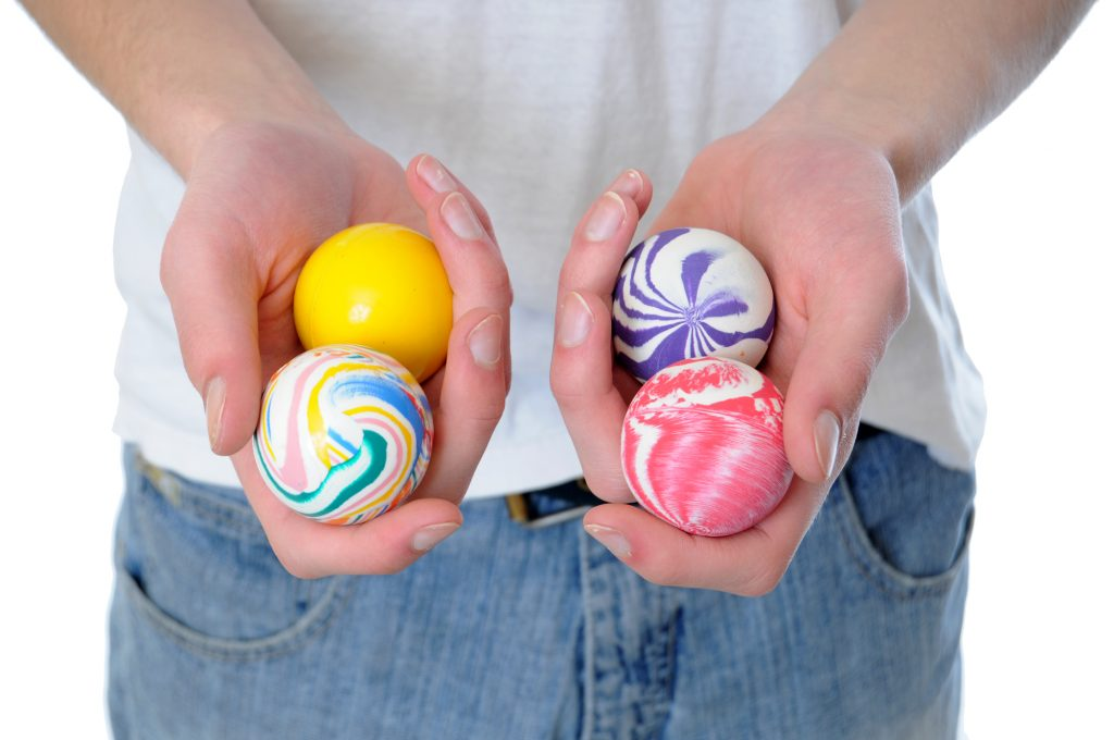 Hand holding a set of four round bouncy rubber balls with colorful designs on them
