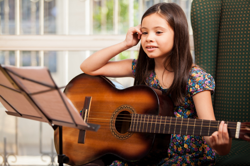 little girl taking guitar lessons as a gift