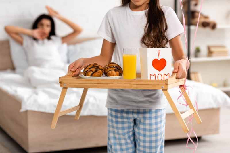 little kid serving her mom breakfast in bed as a gift
