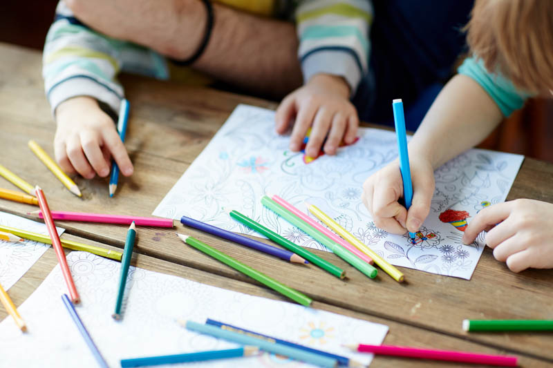 Close-up of children coloring with pencils together